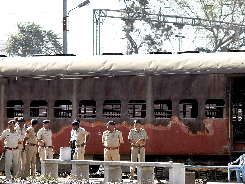 Police stand in front of the charred coach of Sabarmati Express. Image: PTI