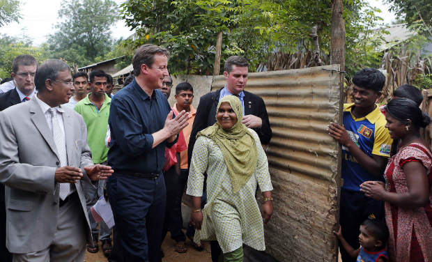 British Prime Minister David Cameron greets villagers of Internally displaced people's camp at Chunnakam village, in Jaffna on Friday - AP