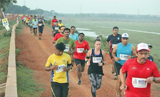 Participants of the trail run organised by Chennai Trekking Club pacing through fields on Sunday.