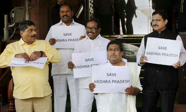 TDP members display placards for united Andhra Pradesh at Parliament House during the extended winter session in New Delhi on Thursday - PTI