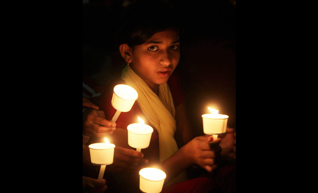 girl takes part in a candle light vigil against child abuse in