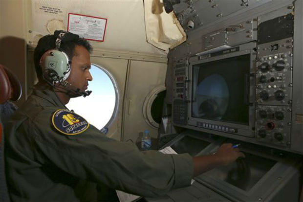 In this Wednesday, March 26, 2014 photo, Tactical Coordinator Imray Cooray operates from his station on board a Royal Australian Air Force AP-3C Orion during a search for the missing Malaysia Airlines Flight 370 in the southern Indian Ocean. A